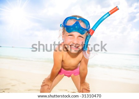 a little girl with snorkel and diving mask at the beach