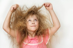 a little girl with tangled long hair in a pink dress on a white background tries to comb it. naughty hair portrait woman with a comb doesn't know what to do
