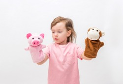 A little girl with toys on her hands on a white background with an open seat. Cute Girl playing with toys in the hands of a Puppet theater.