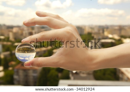 a little glass ball in a hand under the city