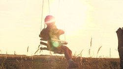 A little happy child is riding high on a swing with a friend teddy in his arms dreaming about flying. Childrens play with a bear outdoors. Kid soars against the sky in the glare of the sun. To