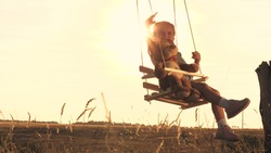 A little happy child is riding high on a swing with a friend teddy in his arms dreaming about flying. Childrens play with a bear outdoors. Kid soars against the sky in the glare of the sun.