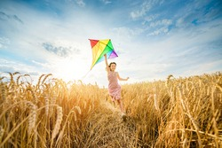 A little happy girl runs with a kite across a ripe wheat field. Harvesting, prosperity, fertility, wealth, a successful future. Happy summer vacation.