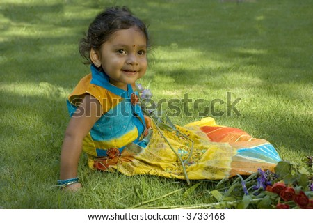 A little Indian girl in traditional dress plays in the grass with flowers.