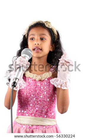 little Indian girl singing with a mic, on white studio background ...