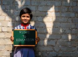 A little Indian Rural Girl holding a Green Board written