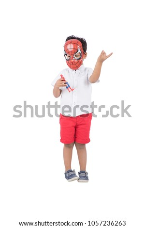 A little kid doing the spiderman movement with his hand and holding a little toy for spider man character and putting his mask, isolated on a white background.