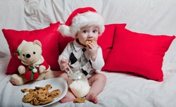 A little kid in a red cap eats a cookies and milk. Christmas photography of a baby in a red cap. New Year holidays and Christmas.