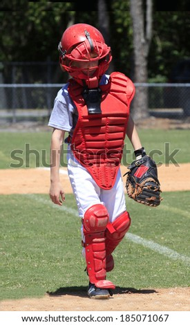 A Little League Catcher in all of his Protective Gear Walks to the Plate for the Big Game