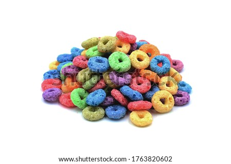 Photo of  A little pile of sweetened corn cereals/shaped like colored rings on white background (isolated)
