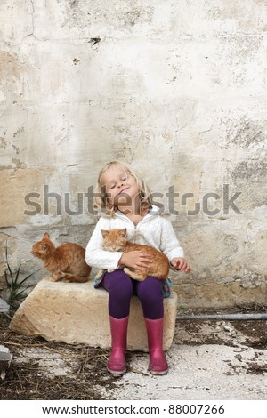 A little preschool child holding a cat, with her eyes closed, sitting against a wall on a farm