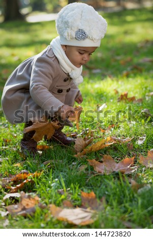 A little pretty happy african child (gir)l playing in autumn park