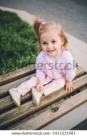 A little pretty little girl in pink pants plays on the waterfront of the lake #1411231481