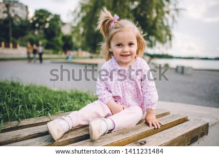 A little pretty little girl in pink pants plays on the waterfront of the lake #1411231484