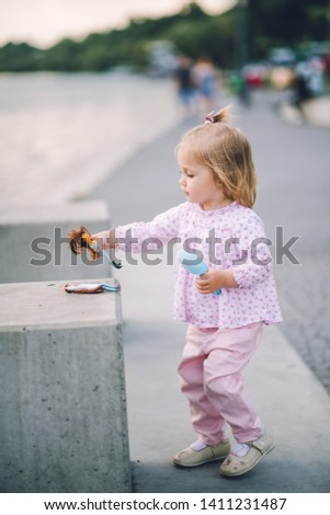 A little pretty little girl in pink pants plays on the waterfront of the lake #1411231487
