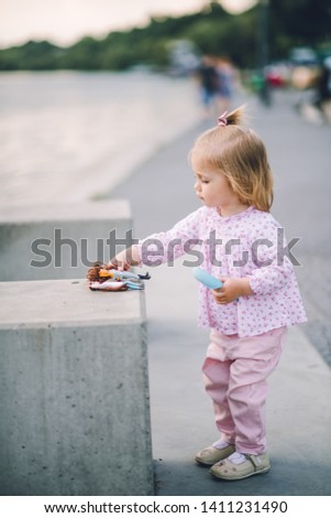 A little pretty little girl in pink pants plays on the waterfront of the lake
