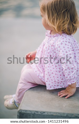 A little pretty little girl in pink pants plays on the waterfront of the lake #1411231496
