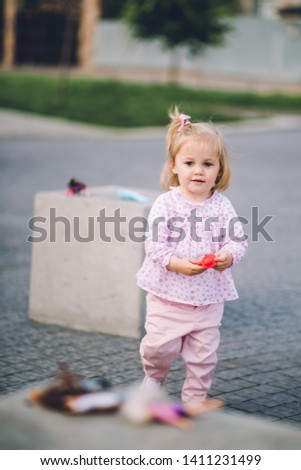 A little pretty little girl in pink pants plays on the waterfront of the lake #1411231499