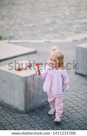 A little pretty little girl in pink pants plays on the waterfront of the lake #1411231508