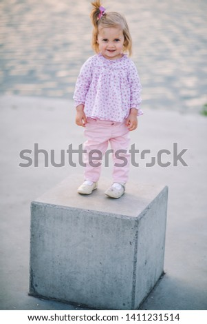A little pretty little girl in pink pants plays on the waterfront of the lake #1411231514