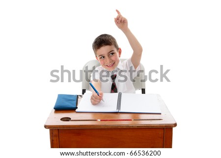 A little school boy student sitting at desk and with one hand up to answer or ask a question.  White background.