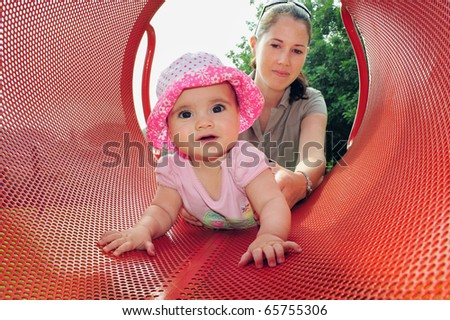 A little six month old baby girl plays with her mom in a playground.  Concept photo of motherhood, newborn, baby, relationship, parenting, love ,care.