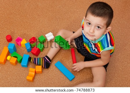 A little smiling boy sitting on the floor is playing his toy blocks