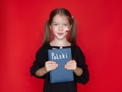 a little smiling cute girl in a black sweatshirt, holding a notebook or book, a Polish flag is painted on her cheek. Advertising concept for learning Polish