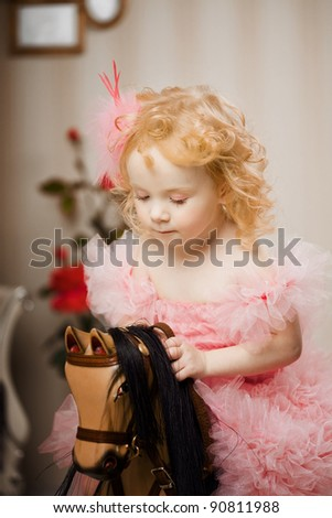 A little sweet girl, a child in a pink dress on a toy horse