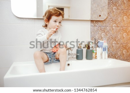 a little sweet little girl with short hair and a white sweater sitting at home in the bathroom on the sink and brushing her teeth with a large blue toothbrush.