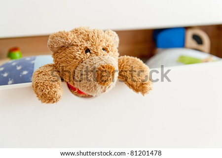 A little Teddy looking out of his drawer with some more toys in the background