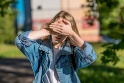 A little teenage girl covered her eyes with her hands. In summer in the open air. A bright sunny day. The concept of reluctance to see. Very bright sun. The game of hide and seek After school.