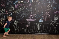 a little three-year-old boy runs near a large slate wall with multi-colored chalk drawings. European appearance
