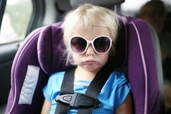 A little toddler child is pouting as she sits buckled into the safety restraint harness of a car seat.