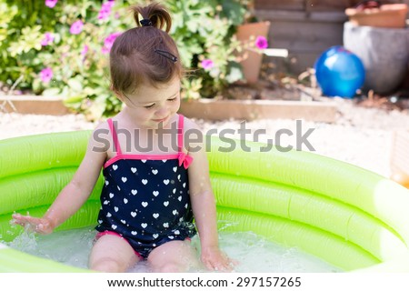 A little toddler girl in a black swimsuit playing in a green paddling pool in the garden