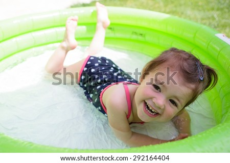A little toddler girl in a black swimsuit playing in the pool in the garden