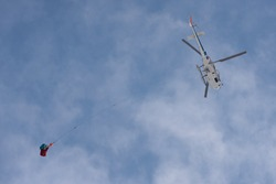 A load-carrying helicopter against a blue, cloudy sky. Cargo suspended on a long rope.