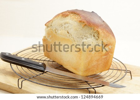 A loaf of freshly-baked homemade bread straight from the tin, cooling on a rack.