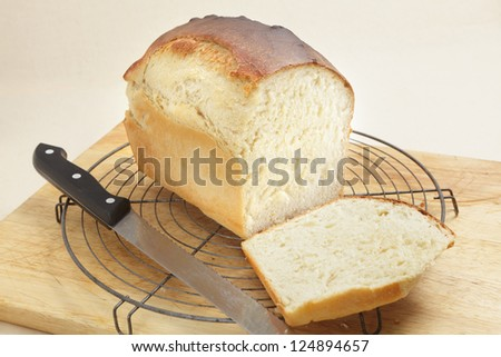 A loaf of freshly-baked homemade bread with the end cut from it to show the texture