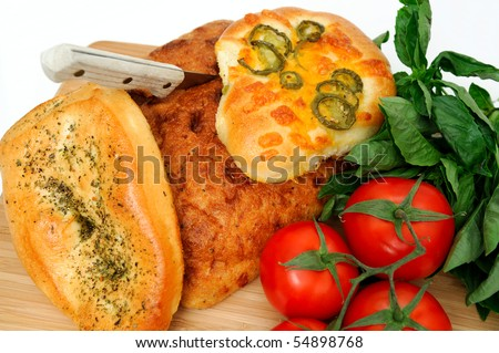 A loaf of old style unsliced bread with  Focaccia topped with Italian herbs and jalapeno with cheddar cheese.