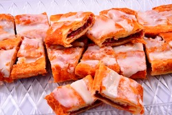 A local Danish pastry treat the Kringle is cut into single serve sizes and laid out on a clear try with a white background. The raspberry Kringle is glazed with icing for that sweet Racine Wi treat.