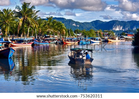 A local fisherman goes out on a boat from boats park to the sea for fishing. Traditional colorful asian fishing boats in fishing village. Langkawi island, Malaysia. #753620311