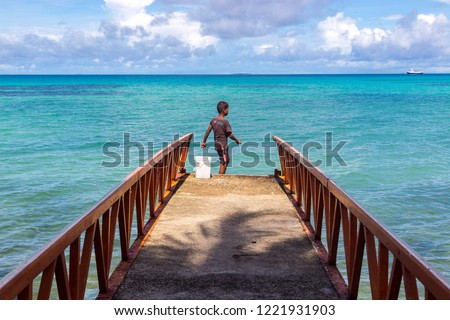 A local Polynesian boy fishing from a jetty pier in a tropical azure turquoise blue lagoon at Vaiaku village, Fongafale motu, Funafuti atoll. Tuvalu, Polynesia, South Pacific Ocean, Oceania.