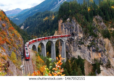 A local train of Rhaetian Railway coming out of the tunnel in a cliff & crossing famous Landwasser Viaduct over a deep gorge with fall colors on the rocky mountainside in Filisur, Grisons, Switzerland #1467052151