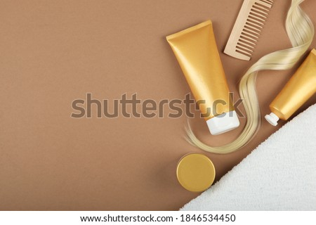 A lock of blonde hair, hair care products and a comb on a colored background top view. set of cosmetics for hair care