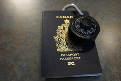 A lock on a Canadian passport. Theme of refugee crisis or open borders