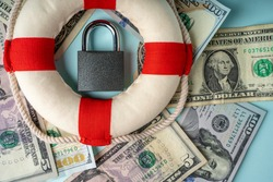 A locked lock on banknotes and a lifeline as a concept of financial security of deposits and money storage