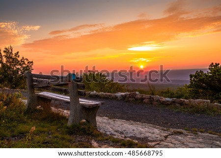 A lone bench looks over the mountain at sunset at the top of New Jersey, High Point State Park