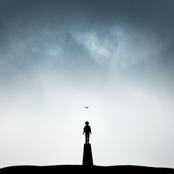 A lone boy standing in silhouette on a trig point beneath brooding clouds with a seagull flying overhead
