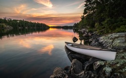 A lone canoe sits on shore on a peaceful lake at sunset. The odd colored clouds in the background are from a forest fire in Northwest Ontario, Canada in the summer of 2018.